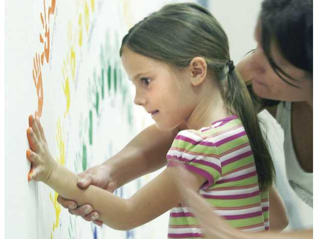 PTA President Paula Allen, right, assists Starlynn Hartnek, 7, as she joins more than 200 people who placed their handprints on the Mitchell Elementary wall mural as part of a school fundraiser Wednesday.