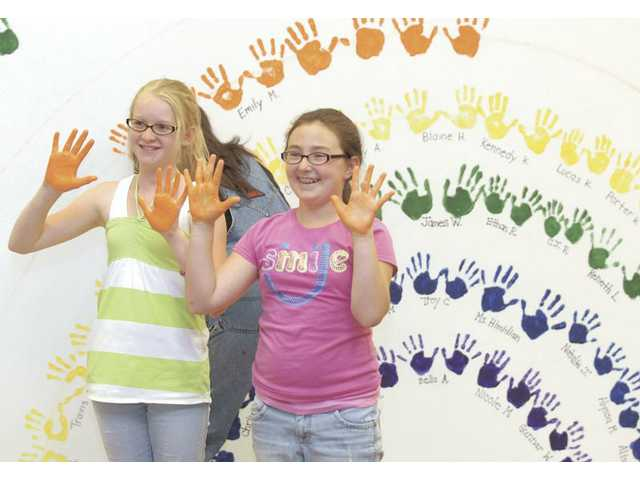 Sixth-graders Carly Wesolowski, left, and Emily Miller display their hands covered with orange paint for a family member's photo as they joined the estimated 200 people who paid to put their hand prints on the Mitchell Elementary wall mural as part of a school fundraiser on Wednesday.