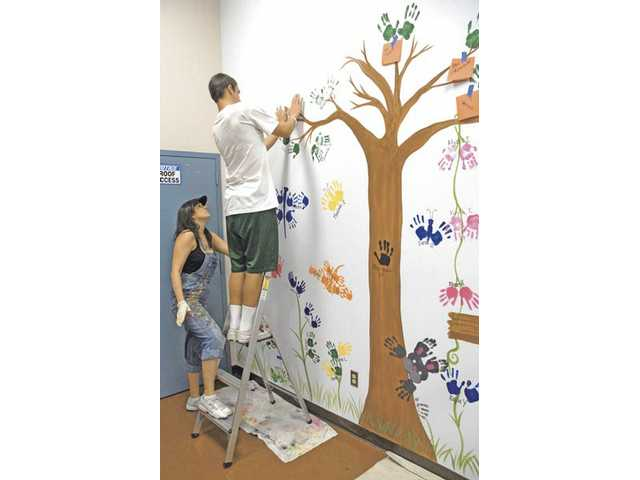 Artist Kym Cappi, left, of Kym's Kreations directs T.J. Yonkers, 16, on the ladder, as he places his hand prints to form leaves of a tree in a garden setting.