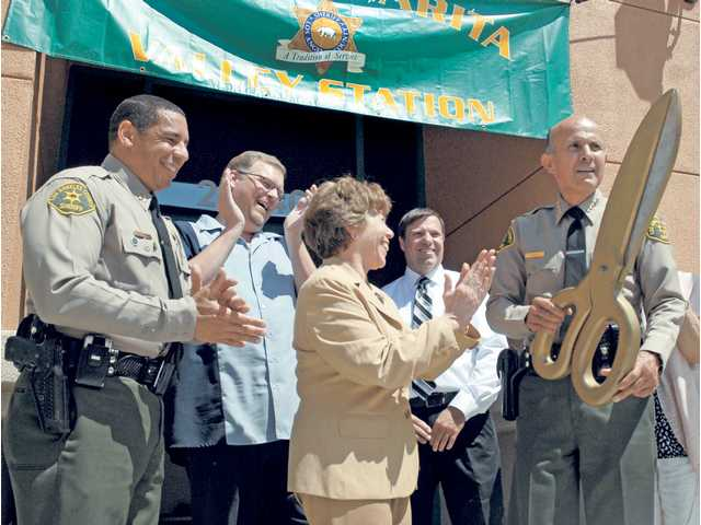 From left, Santa Clarita sheriff's Captain Anthony La Berge, Mayor Frank Ferry, Councilmember Marsha McLean, and Lt. Stephen Low applaud as Sheriff Leroy Baca cuts the ribbon to open the new Santa Clarita Valley Sheriff's Station's Detective Bureau at a grand opening ceremony Wednesday.