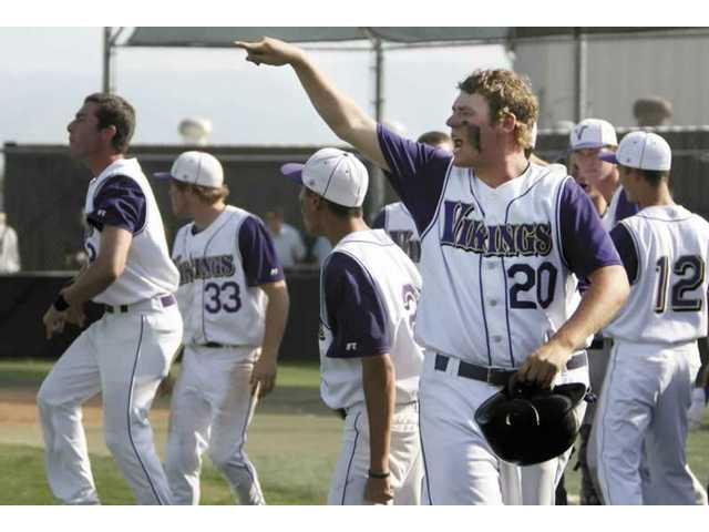 Valencia High first baseman Matt Higgins (20) and other teammates cheer on Robbie Mouselli who doubled in two runs in the bottom of the sixth inning. The Vikings went on to defeat Lakewood, 4-0, to advance into the CIF-Southern Section Division I quarterfinals.