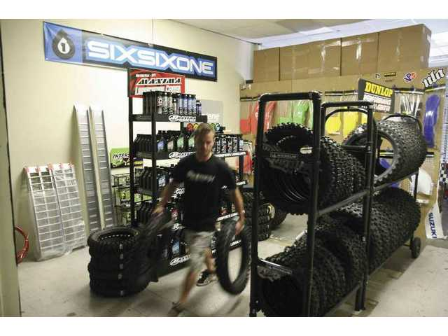 Factory MX owner Ryan Alexy carries tires through the second room of his Canyon Country store, Factory MX, which opened its doors on April 17 and held its official grand opening celebration last Saturday.
