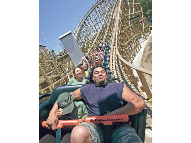 Tevita Taufanema, of Canyon Country, holds his 9-year-old daughter Nalaii as they sit front seat of the new Terminator Salvation The Ride during media day at Six Flags Magic Mountain Thursday morning.