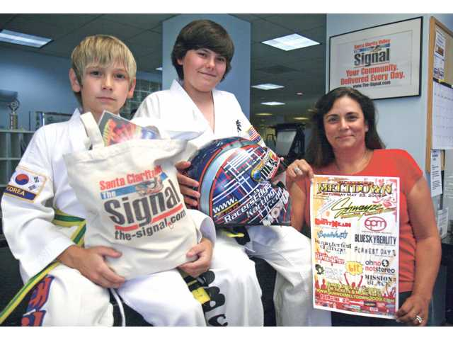 Racer's Edge Summer Meltdown Ultimate Giveaway winner Johnny Flinn (center), with brother Jordan (left) and mother Judi, shows off his prize package during a visit to The Signal Thursday.