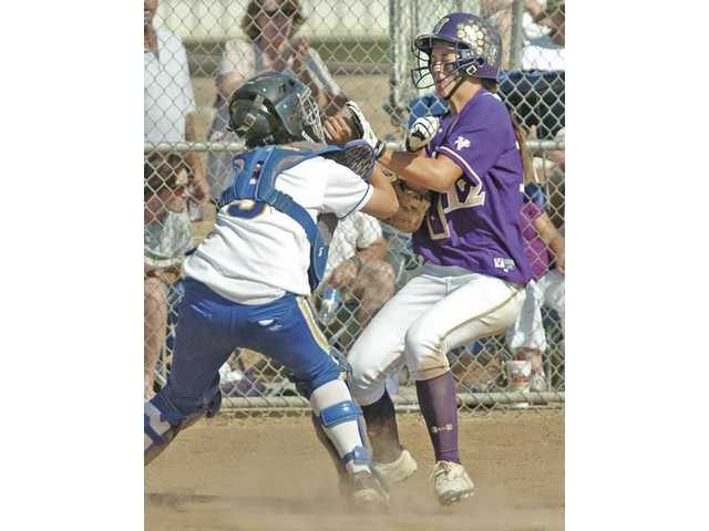 Valencia's Megan Fogelsang (12) collides with Aurora catcher Samantha Smirk (9) during a game at Valencia High Thursday.