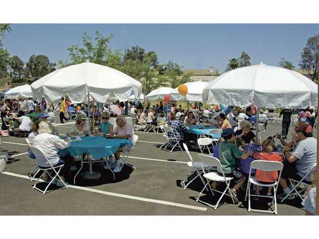 People from the Santa Clarita and San Fernando valleys sit and enjoy authentic Jewish dishes at the first Jewish Food Festival at the Bridgeport Marketplace on Sunday.