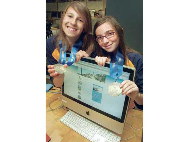 Castaic Middle School sixth-graders Andrea Marroquin, left, and Kyla Resnick display the second-place medals they earned in the Constitutional Rights Foundation's statewide competition. Their project was a website they designed about the Los Angeles Aqueduct.