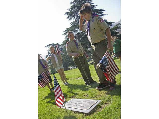 Fourteen-year-old Henry Johnson, of the Canyon Country's Elk Lodge troop 2379, honors a deceased soldier at Eternal Valley Memorial Park Saturday morning. Local scouts placed 5,012 American flags to honor those who served in the armed forces.