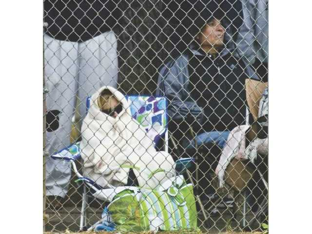 Jennifer Moniz sits bundled up during the Hart High vs. Long Beach Wilson High baseball game, watching her son Spencer Moniz in the fifth inning. Temperatures will be a bit warmer this weekend.