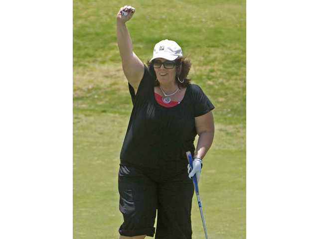 Denise Kennedy celebrates a successful putt at the annual Zonta tournament.