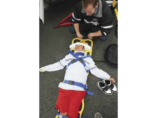 American Medical Response EMT Aaron Kanes demonstrates the spinal board on Sequoia Charter School eighth-grader, Jordan Zavala, during career day Friday.