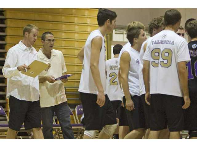 Valencia assistant coach David Neeley, far left, consults with head coach Mark Knudsen during a timeout Friday against Royal at Valencia High.