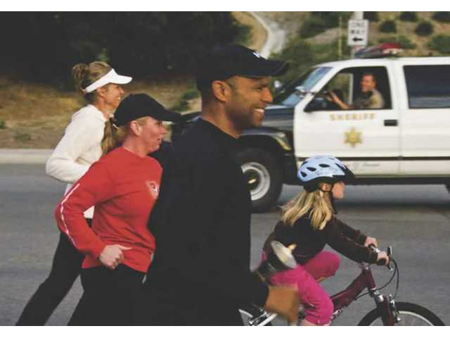 Sgt. Byron Wainie of the Santa Clarita Valley Sheriff's Station runs during the 31st Annual Memorial Torch Run Relay on Saturday. The three-day event, held across Los Angeles County, honors peace officers who lost their lives while on duty.