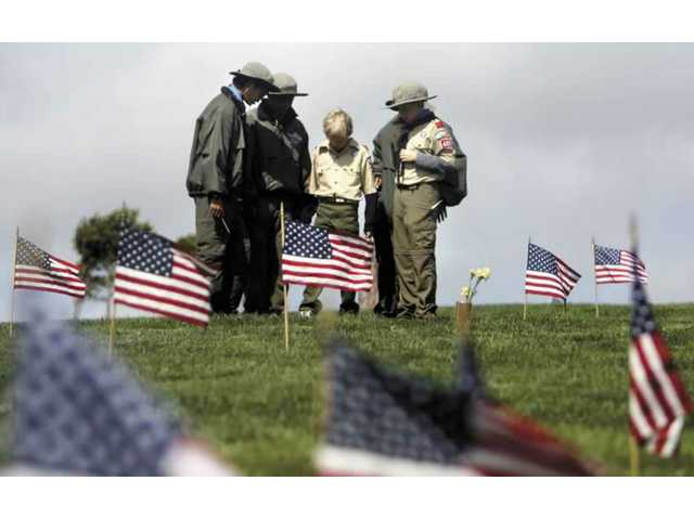 A group of local Boy Scouts from Troop 499 pay respects to a veteran after placing a flag near his grave on Saturday morning at Eternal Valley Memorial Park. Boy and Girl Scouts from all over America are invited to this annual event in preparation for Memorial Day.