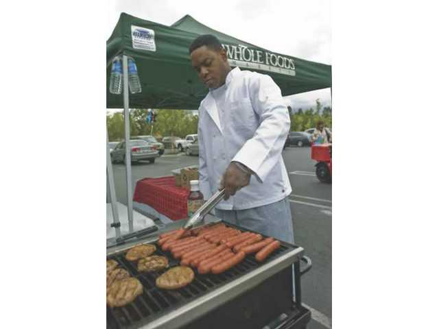 Byron Webster, chef and creator of Jimmy Bo's Famous BBQ Sauce grills up some burgers and hot dogs at Whole Foods.The barbecue was part of the free Red, White, and Blue Memorial Day event where Whole Foods showed off some of their barbecue ideas and products