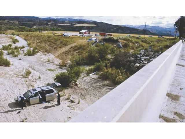 CHP officers inspect the Honda Odyssey that landed in the Castaic Creek riverbed after running through a barrier on the bridge and crashing over the rocks shown at right. The driver of the vehicle and one of the children who were passengers had serious injuries.