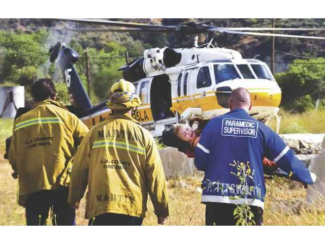 Two L.A. County firefighters and a paramedic carry two children over to a helicopter for transport to UCLA Medical Center.