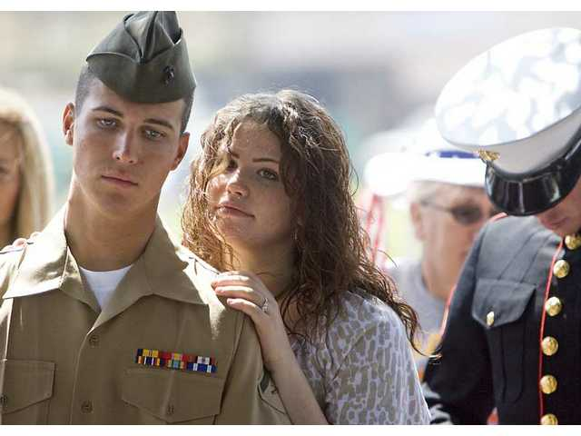 Valencia resident Lexi Reeve, 19, embraces her Marine boyfriend Daryl Crookston, 20, during the 21st annual Memorial Day Tribute at Eternal Valley Memorial Park on Monday morning.