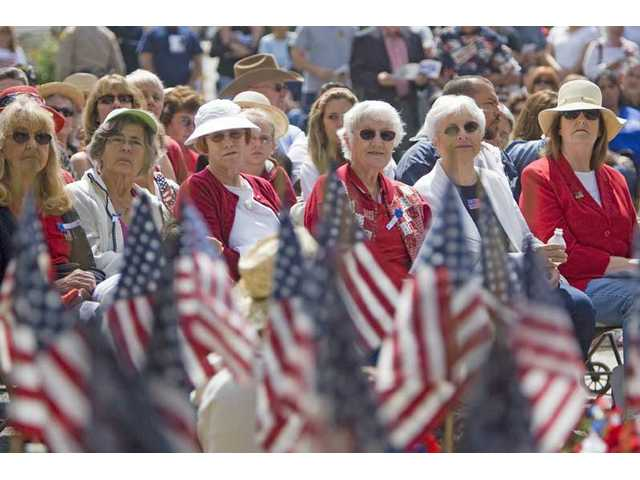 A group of women listen to tributes made to war veterans during the 21st Memorial Day Tribute at Eternal Valley Memorial Park Monday morning.