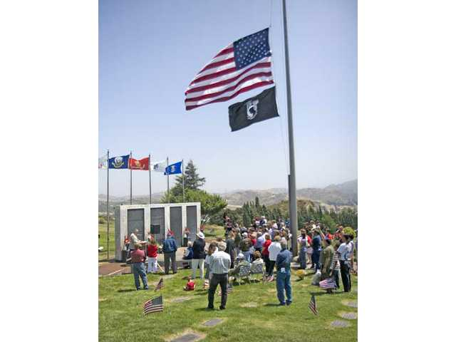 Locals stand on top of the hill at Eternal Valley Memorial Park as more than 850 SCV veteran names were read aloud at the Memorial Wall on Monday morning.