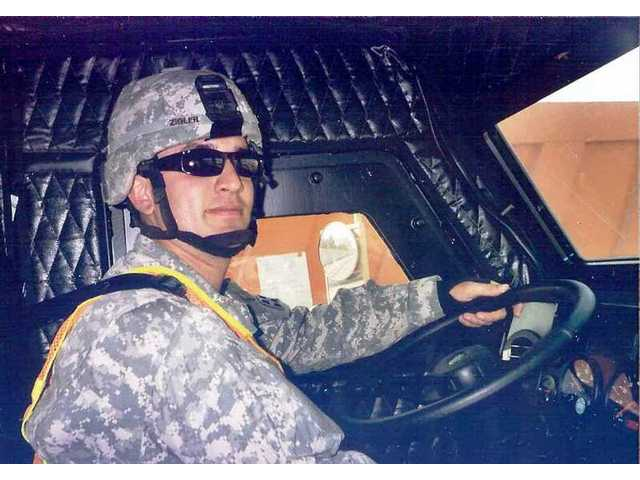 U.S. Army combat engineer PFC Jason Zigler takes the wheel of a Humvee used in military escorts of civilian trucks carrying equipment and supplies into the Iraqi war zone.
