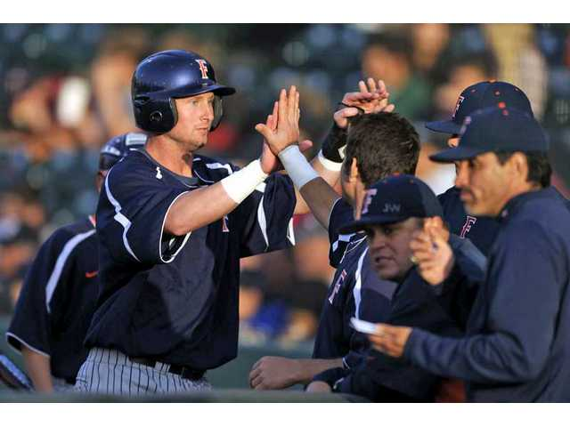 Cal State Fullerton senior Jared Clark, left, is congratulated by his teammates during a 2009 game.