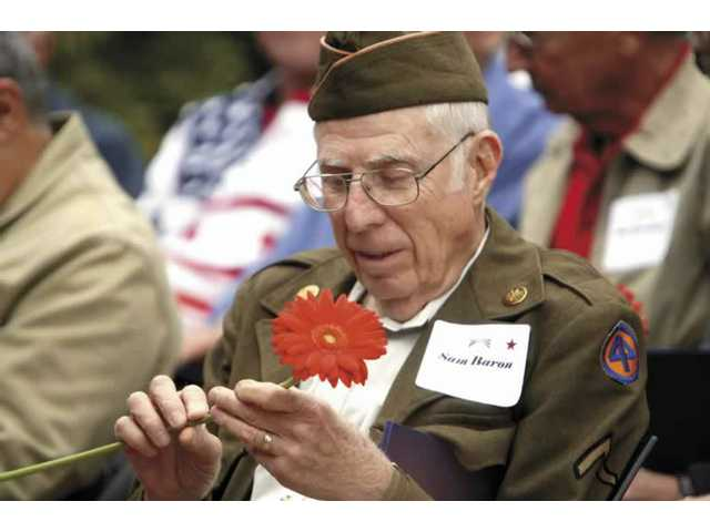 Sam Baron, a resident of Belcaro in Valencia, looks at a flower given to him by the Veterans Day Memorial Committee.