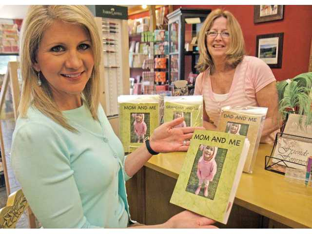 Sandra Mitchell, left, shows off one of the currently available Sobo Cards designs. The cards are carried at Valencia's Paper Mulberry store, owned by Patti Fincher, right. Mitchell, an award-winning journalist and KCAL 9 news anchor, and her husband, Nehl Bobal, a comedy writer, launched Sobo Cards
