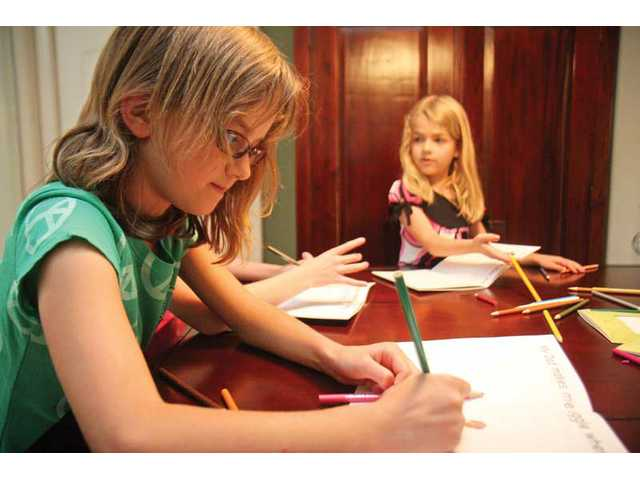 Jenna Roth, 9, and 6-year-old sister Lexi Roth draw and write on customized Father's Day Sobo Cards as a unique present for dad.
