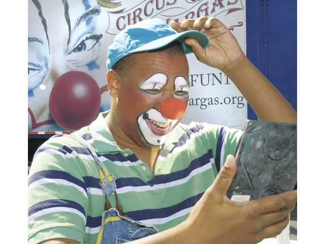 Signal reporter Brian Charles looks in a mirror after being transformed into a Circus Vargas clown on Wednesday.