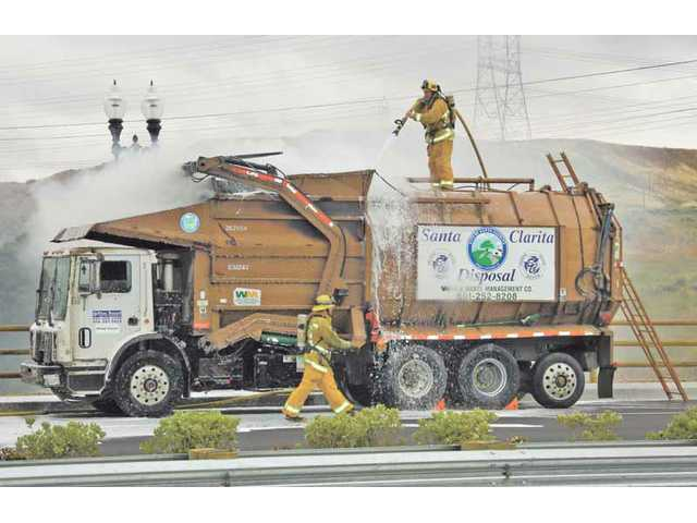 A trash-truck load that caught fire is extinguished on the cross-valley connector on Thursday.