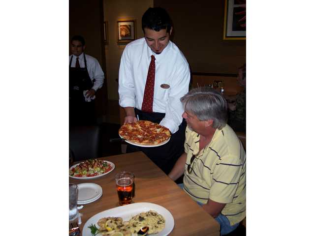 Dennis Poore of Canyon Country is served a Pepperoni Supremo hearth-baked pizza by Adam Dehoyos of Fraizer Park. California Pizza Kitchen hires locally and all servers wear the name of their home community on their name badges. The restaurant opened Monday in Bridgeport Marketplace.