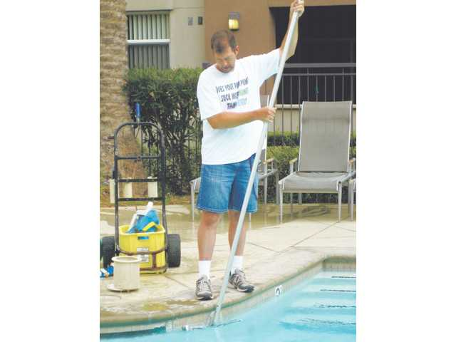 Ben Honadel of Pools by Ben brushes down the side of a pool. Brushing is an important part of pool maintenance.