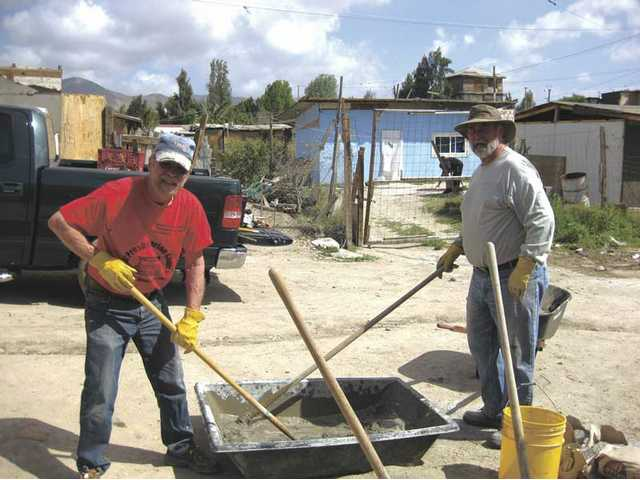 Jay Headley and Don Trammell hand-mix sand, cement and water, making stucco used to coat the outside of the homes.