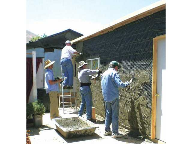 A group who called themselves 'men at work' from First Presbyterian Church, Newhall, apply the first coat of stucco to a home in Tijuana, Mexico as a part of an Amor Ministries mission trip.