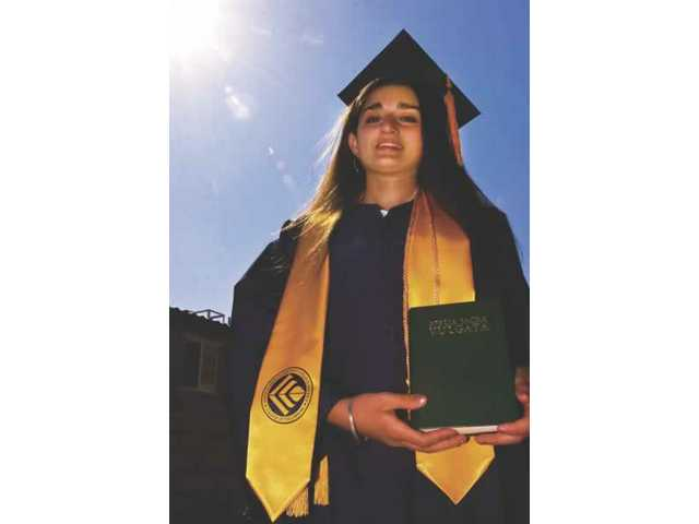 This year's youngest College of the Canyons grad, 16-year-old Natasha Walia, stands in her backyard with the Latin Bible she was given as a gift.