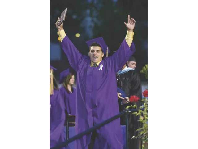 Daniel Peter Guzman walks off the stage after receiving his diploma during Valencia High School's graduation ceremony Thursday night at College of the Canyons.