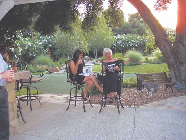 Geri Jacobs and Dianne Crawford peruse the auction catalog under the shade at the home of Richard and Marion Sandnes.