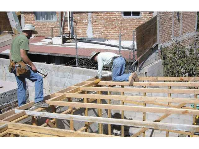 Two members of Men at Work construct a home during their recent trip to Tijuana.