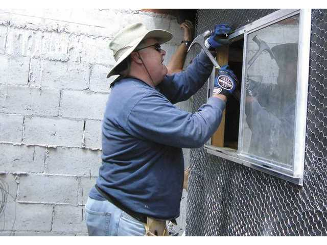A member of Men at Work, the men's group at First Presbyterian Church of Newhall, secures a window of a home in Tijuana as part of their recent mission to the area.