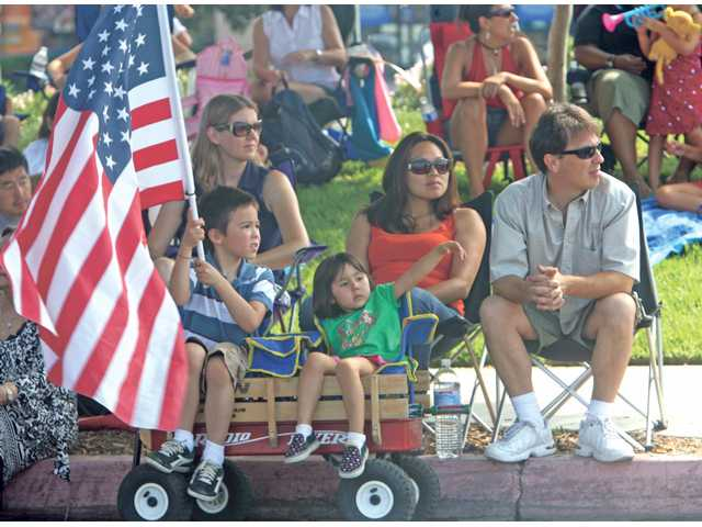 Locals watch the Fourth of July parade under the shade.