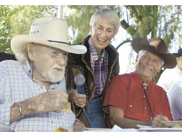 "Harry ""Dobe"" Carey Jr., left, relates a childhood memory of his father to City Councilwoman Laurene Weste, center, and Western actor Ty Hardin at a gathering of family and friends at Tesoro Adobe Park on Saturday."