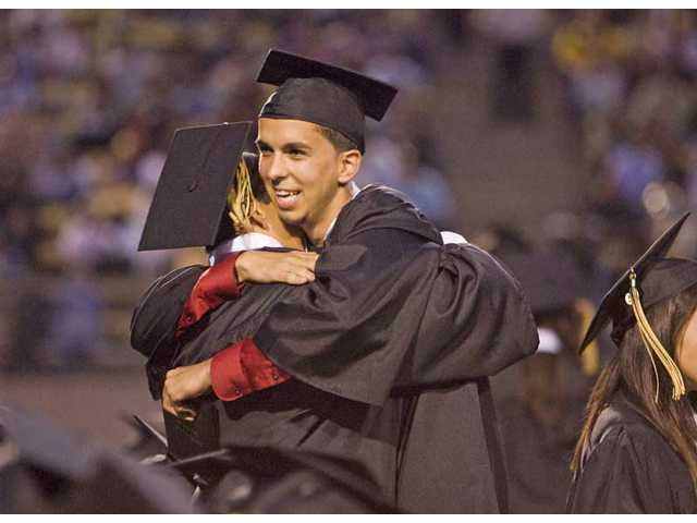 Ibrahim Rassoli hugs a classmate after receiving his diploma Monday evening at College of the Canyons' Cougar Stadium for the 2009 Golden Valley High School commencement ceremony. More than 400 students graduated Monday night.