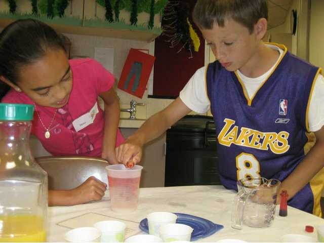 Diana Canchola, left, and Cody Meadows measure out the ingredients that go into a 12-ounce soda. A group of Canyon Springs Elementary School fourth-graders have spent the school year spreading tips for healthy eating habits.