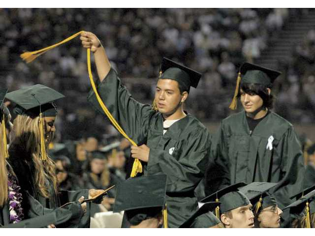 Kyle Cooper swings a graduation cord like a cowboy after receiving his diploma at the Canyon High School graduation ceremony at College of the Canyons on Tuesday.
