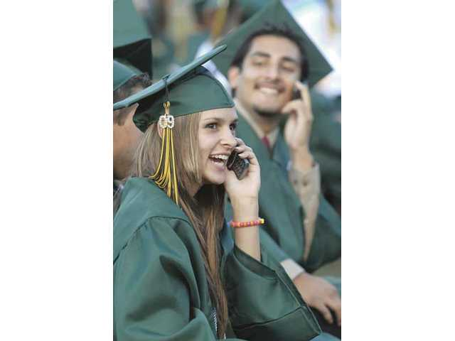 Tamara Abbene, left,  and Oscar Alcala talk to relatives in the stands on their cell phones as they wait for Canyon High School's graduation ceremony at College of the Canyons to begin.