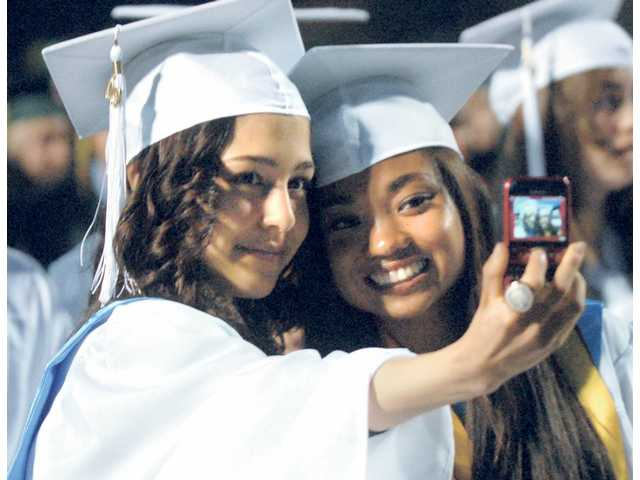 Canyon High School seniors Alexandra Vatchkova and Leah Carrillo take a photo with a cell phone as they wait for graduation ceremonies to begin at College of the Canyons on Tuesday.