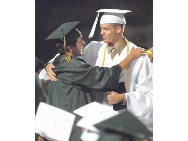 Canyon High graduates Michael Mance and Michael Edwards congradulate each other after receiving their diplomas at graduation ceremonies at College of the Canyons on Tuesday.