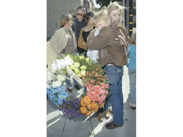 Phil Rawlin's wife, Fran gets a hug from Councilwoman Laurene Weste at a memorial wreath ceremony for western screen stuntman Phil Rawlins on the site of his 2007 Newhall Western Walk of Stars plaque on Market Street in Newhall on Tuesday afternoon. Phil Rawlins died quietly at home in Placerita Canyon on Thursday at the age of 79.
