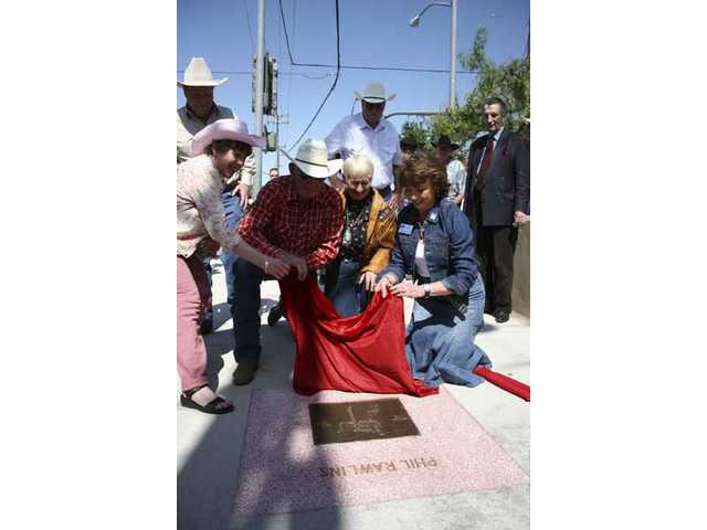 Phil Rawlins (plaid shirt) unveils his plaque on the Western Walk of Stars in Old Town Newhall on April 27, 2007, with a little help from (left to right): Bob Kellar, Santa Clarita City Councilman; Marsha McLean, then Santa Clarita Mayor; Laurene Weste, Santa Clarita City Councilwoman; Jack Lilley (center, white shirt), a boyhood friend of Rawlins; Pam Ingram, then-chair of the SCV Chamber of Commerce; and Harry Dean Stanton (standing), also a 2007 inductee.